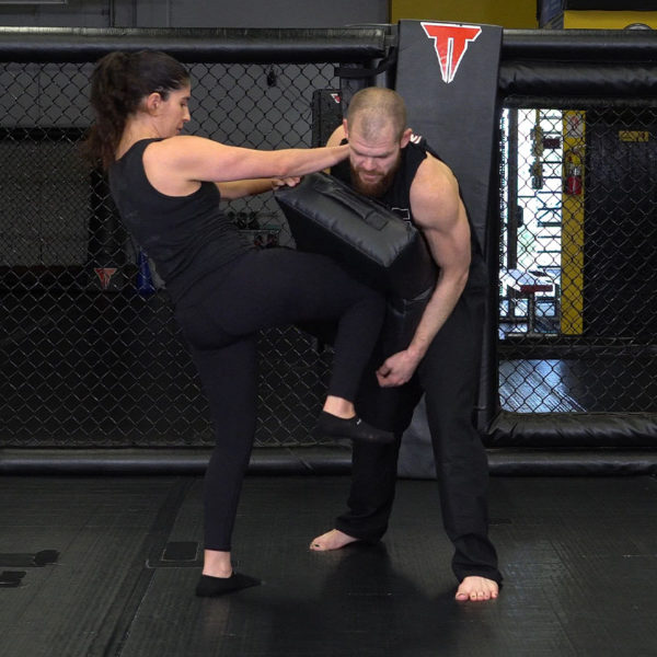 woman throwing a knee on kick shield that a man is holding